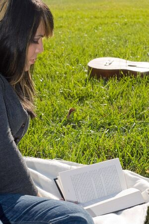 A young woman with highlighted hair reading a book or doing homework on campus. 版權商用圖片