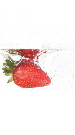 A juicy red strawberry plunging into some water. Shallow depth of field. Stock Photo