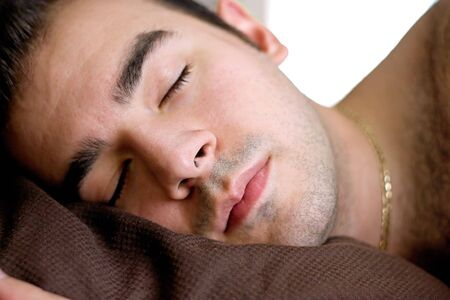 bed sheet: A young man is fast asleep in bed.