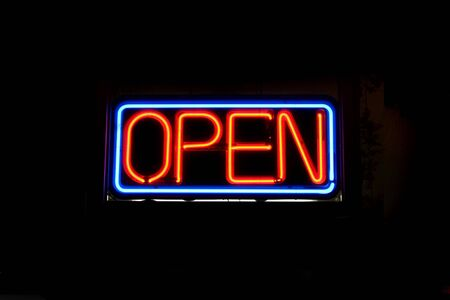 A neon OPEN sign commonly seen in businesses. photo