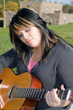 blonde streaks: A young hispanic woman playing a guitar while sitting on a blanket in the green grass. Her hair is highlighted with blonde streaks.