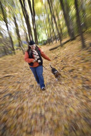 A young woman walking her dog through the woods with a zoom blur effect. photo