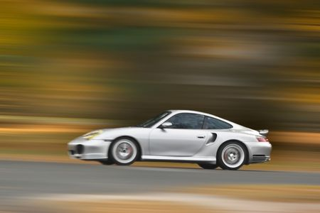zooming: A modern sports car speeding along the road with a motion blur effect.