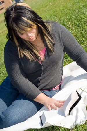highlighted hair: A young woman with highlighted hair reading a book or doing homework on campus. Stock Photo