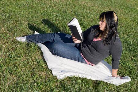 highlighted hair: Una giovane donna con i capelli in evidenza la lettura di un libro o fare a casa nel campus.
