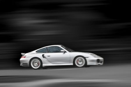 A modern sports car speeding along the road with a motion blur effect - selective color.