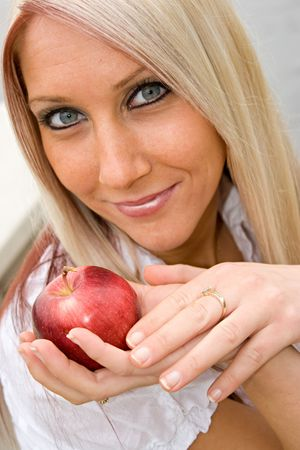 A young blond posing with an apple that she is holding in her hand. Stock Photo - 3847094