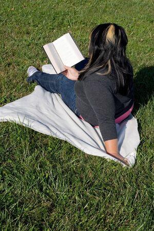 highlighted hair: Una giovane donna con i capelli in evidenza la lettura di un libro sul campus della scuola. Archivio Fotografico