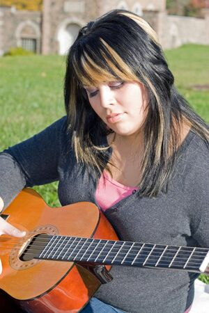 highlighted hair: A young hispanic woman playing a guitar outdoors.