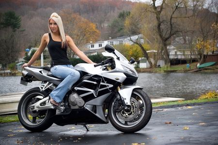 wife beater: A pretty blonde girl posing on a motorcycle.