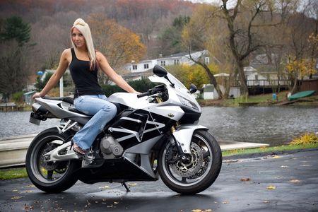 Een mooie blonde meisje poseren op een motorfiets.