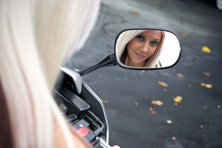 A pretty blonde woman looking into the mirror on her motorcycle. Stock Photo - 3869752