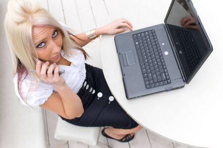 A beautiful young blond woman in a mobile business setting with her cell phone and laptop. Stock Photo - 3869799