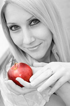 A young blond posing with an apple - black and white with selective color. Stock Photo - 3869828