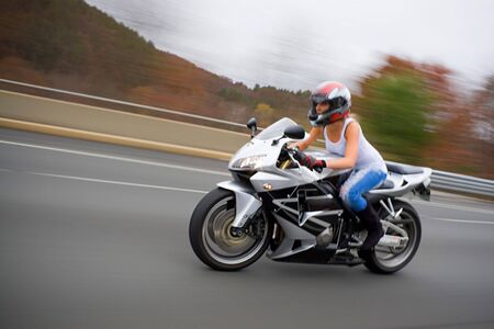 A pretty blonde girl in action driving a motorcycle at highway speeds. Stock Photo - 3869753