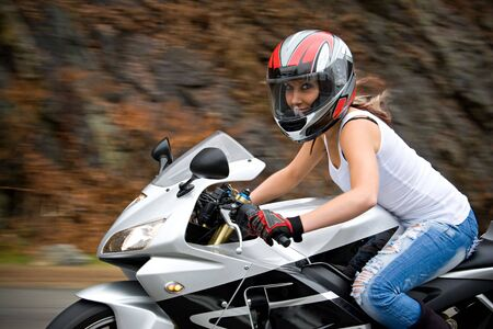 woman motorcycle: A pretty blonde girl in action driving a motorcycle at highway speeds.