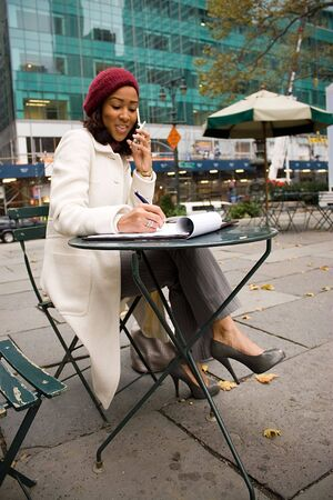 An attractive business woman talking on her cell phone while sitting at a table outdoors. Stock Photo - 3869889