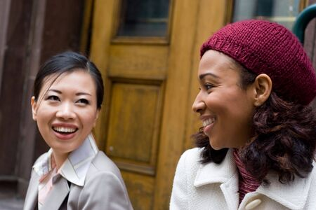 business pitch: Two business women having a casual meeting or discussion in the city.  Shallow depth of field.