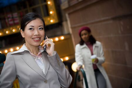An attractive Asian business woman talking on her cell phone in the city. photo