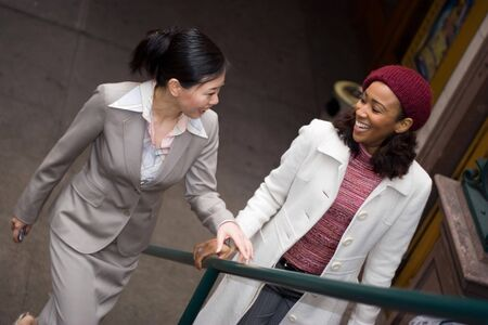 Two business women having a casual meeting or discussion while walking in the city. Stock Photo - 3869812
