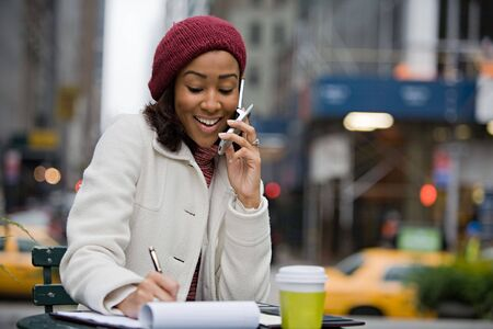 An attractive business woman talking on her cell phone while seated outdoors in the city. Stock Photo - 3869928