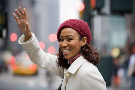winter woman: A pretty young business woman hails a taxi cab in the city.
