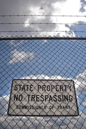 A no trespassing sign that reads STATE PROPERTY NO TRESPASSING outside an airport. photo