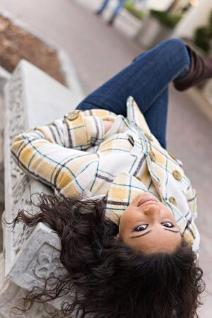 A closeup of a pretty Indian woman laying on a bench outdoors. Stock Photo - 3971548