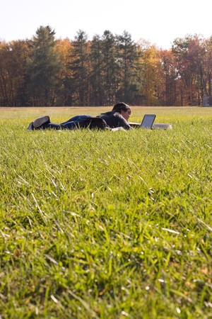 A young student using her laptop computer while laying in a green grassy field. Stock Photo - 3984323