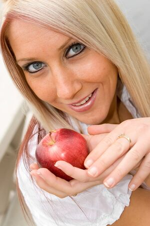 A young blond posing with an apple that she is holding in her hand. Stock Photo - 3984322