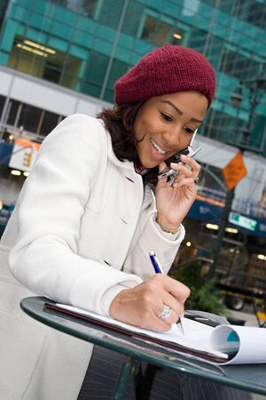 An attractive business woman talking on her cell phone while seated outdoors in the city. photo