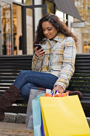 An attractive young woman checking her cell phone while out shopping in the city.