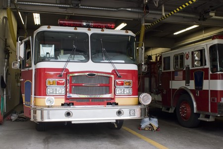 A fire truck is parked in the bay with all of the fire fighting equipment and gear ready to go. photo
