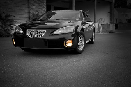 shiny black: A modern sports sedan with selective color parked in an urban setting. Stock Photo