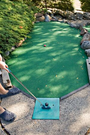 A person getting ready to putt while playing miniature golf. Stock Photo