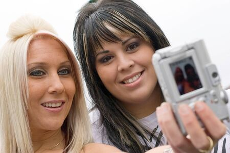 Two young women taking pictures of themselves with a digital camera. Stock Photo - 4020761