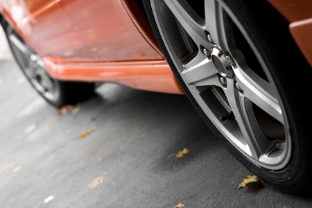 domestic garage: A closeup of the custom rims on a modern sports car with plenty of copyspace.  Shallow depth of field.