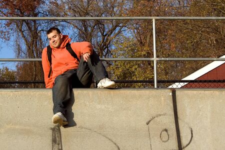 A young man posing at the top of a skateboard ramp. photo