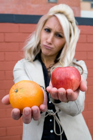 unequal: A young woman compares an apple to an orange. Stock Photo