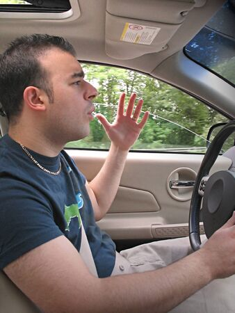 road rage: A young man seems to be experiencing some road rage while driving.
