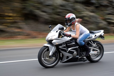 hot wife: A pretty blonde girl in action driving a motorcycle at highway speeds.