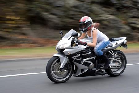 Une jolie jeune fille blonde en action de conduire une motocyclette à vitesse. Banque d'images - 4092126