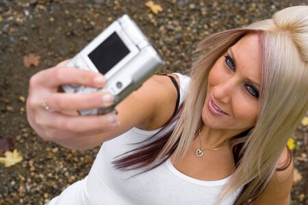 A young woman taking pictures of themselves with a digital camera. photo