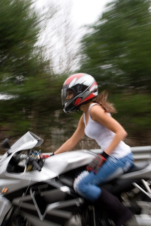 wife beater: Abstract blur of a pretty girl driving a motorcycle at highway speeds.