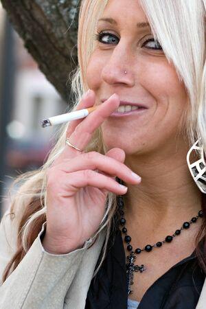 A young blonde woman takes a cigarette break outdoors. 免版税图像