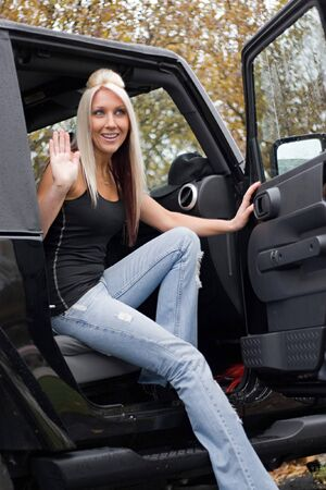 going out: A young woman steps out of the passenger side door of a recreational vehicle. Stock Photo