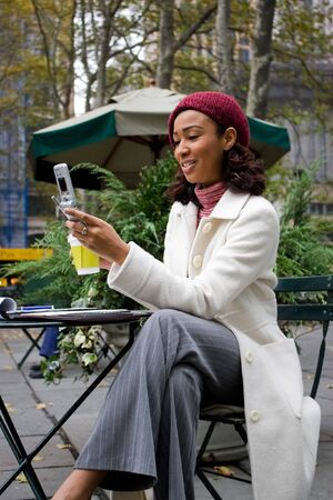 An attractive business woman checking her cell phone in the city.  She could be text messaging or even browsing the web via wi-fi or a 3g connection. Stock Photo - 4153244
