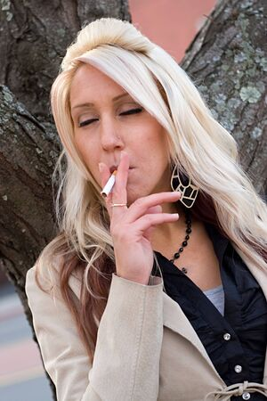 break: A young blonde woman takes a cigarette break outdoors. Stock Photo