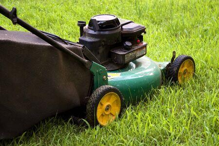 cutting through: A modern lawn mower cutting through the grass. Stock Photo