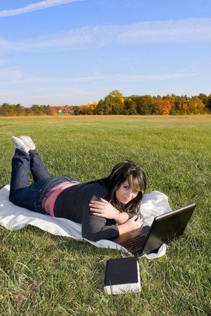 A young student using her laptop computer while laying in the grass on a nice day. photo